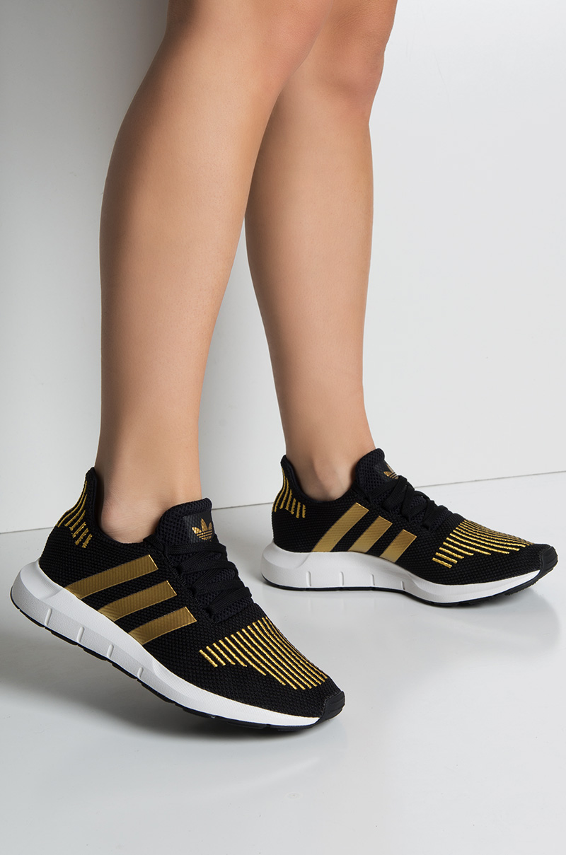 58136ba0bc558 adidas Women s Swift Run Sneakes in Black Gold White